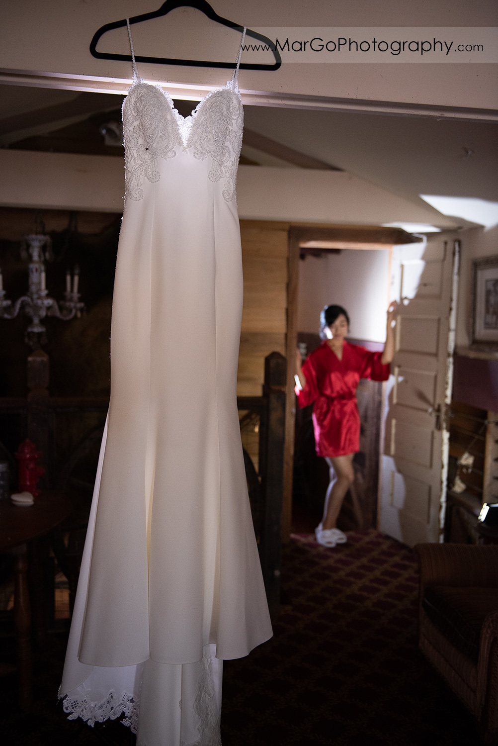 wedding dress hanging from the ceiling with bride in red robe in background at Long Branch Saloon & Farms in Half Moon Bay