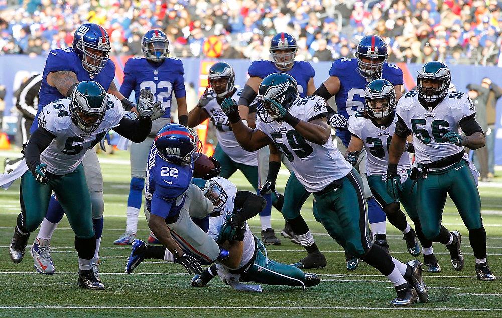 Description of . New York Giants David Wilson (2nd L) is tackled by Philadelphia Eagles Brandon Graham (L), Kurt Coleman (2nd R) and DeMeco Ryans (R) in the first quarter during their NFL football game in East Rutherford, New Jersey, December 30, 2012. REUTERS/Gary Hershorn