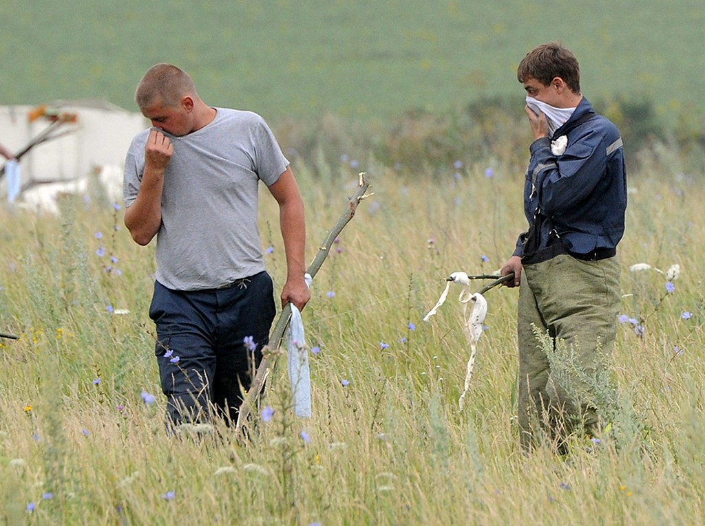 . People search for bodies on July 18, 2014 at the site of the crash of a Malaysian airliner carrying 298 people from Amsterdam to Kuala Lumpur, near the town of Shaktarsk, in rebel-held east Ukraine. Pro-Russian separatists in the region and officials in Kiev blamed each other for the crash, after the plane was apparently hit by a surface-to-air missile. All 298 people on board Flight MH17 died when the plane crashed. Rescue workers at the crash site said that they had found one of the black boxes from the passenger liner. AFP PHOTO/DOMINIQUE FAGET/AFP/Getty Images