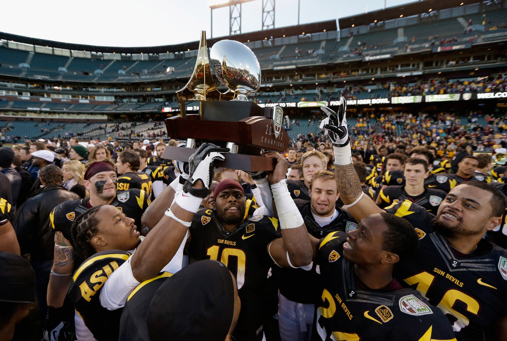 Description of . Players from the the Arizona State Sun Devils lift the trophy after they beat the Navy Midshipmen in the Kraft Fight Hunger Bowl at AT&T Park on December 29, 2012 in San Francisco, California.  (Photo by Ezra Shaw/Getty Images)