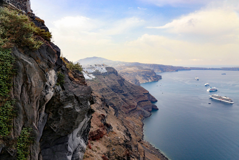 A coastal shot of cliffs and sea with cruise ships in the distance on a cruise to Santorini