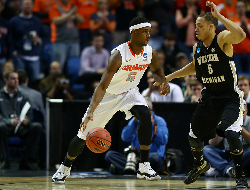 . BUFFALO, NY - MARCH 20: C.J. Fair #5 of the Syracuse Orange drives to the basket as David Brown #5 of the Western Michigan Broncos defends during the second round of the 2014 NCAA Men\'s Basketball Tournament at the First Niagara Center on March 20, 2014 in Buffalo, New York.  (Photo by Elsa/Getty Images)