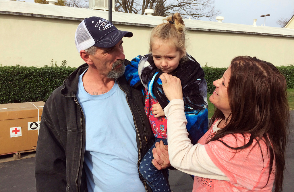 . Oroville, Calif., resident Patrick Cumings, left, holds his daughter, Elizabeth, and he stands with his wife, Elizabeth Cumings at the Red Cross evacuation center in Chico, Calif., Monday, Feb. 13, 2017. The water level has dropped behind the Oroville Dam, nation\'s tallest dam, in Oroville reducing the risk of a catastrophic spillway collapse and easing fears that prompted the evacuation of the Cumings and others downstream. (AP Photo/Don Thompson)