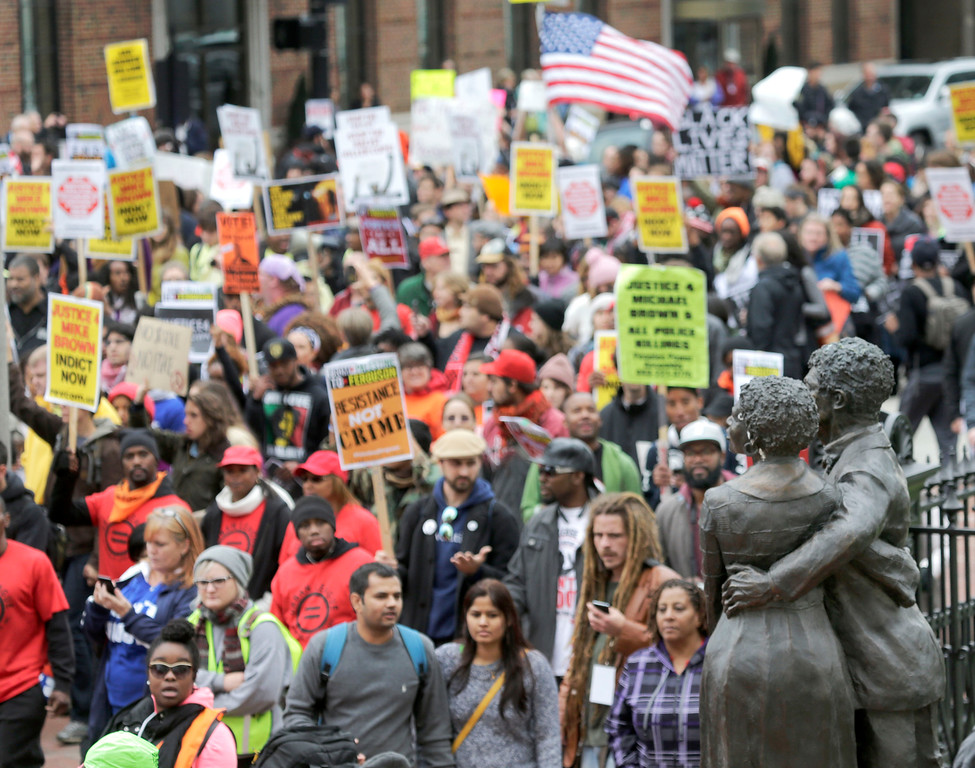 . Protesters march past the statue of Dred and Harriet Scott at the historic federal courthouse, during a march against gun violence and the shooting of Ferguson, Mo., teenager Michael Brown, Saturday, Oct. 11, 2014, in St Louis.  Saturdayís crowd appeared larger than the ones seen at Fridayís protests, and while the main focus of the march thatís scheduled to wind through downtown streets for several hours is on recent police shootings, participants embraced other causes such as gay rights and the Israeli-Palestinian conflict. Police officers were stationed around the area.   (AP Photo/Charles Rex Arbogast)