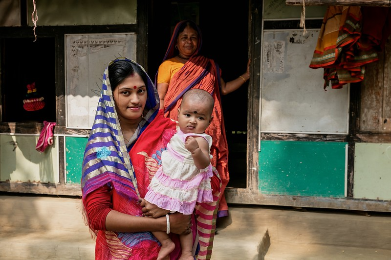 0108-0116Songita Rani (20) posing for family photo with her husband Sumon Shil (26) & six month old daughter Anusree in front of the Courtyard.Atkhali Village, Dakua Union Golachepa, Potuakhali. Bangladesh.Photo Credit: b.a.sujaN / Map / WRA