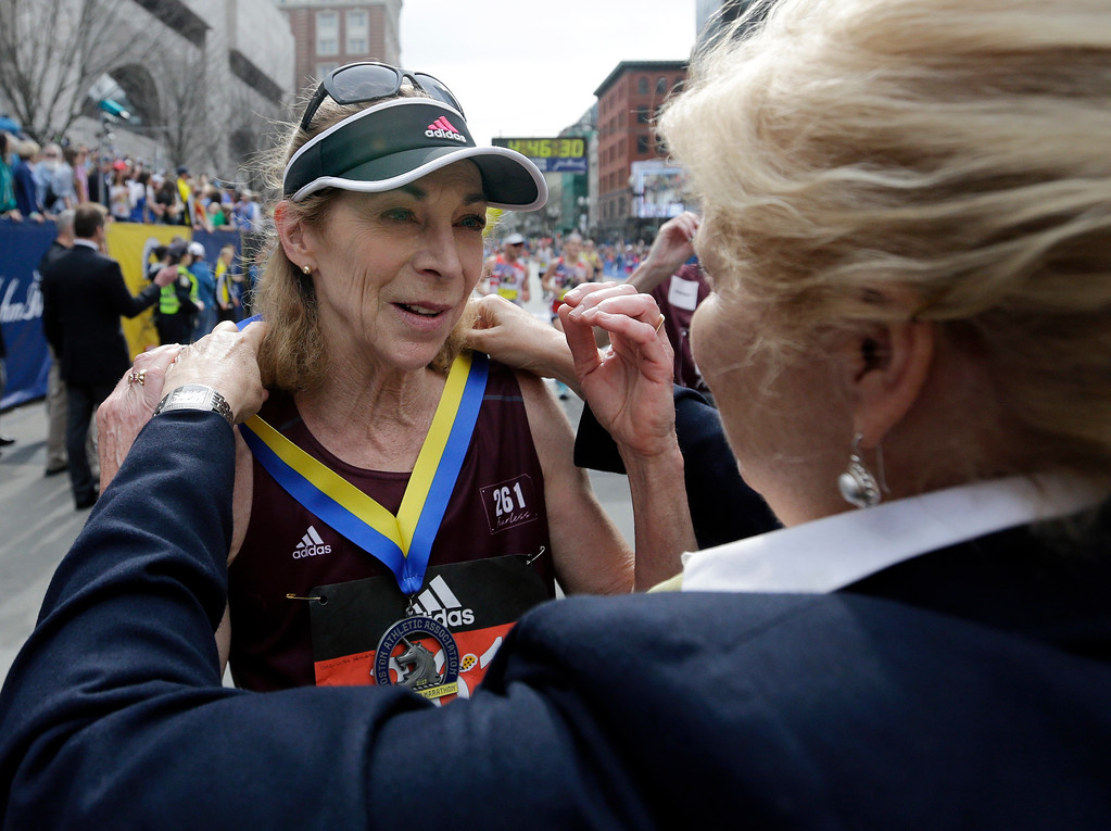 . Kathrine Switzer, who was the first official woman entrant in the Boston Marathon 50 years ago, receives her medal from Joann Flaminio, right, of the Boston Athletic Association after finishing the 121st Boston Marathon on Monday, April 17, 2017, in Boston. (AP Photo/Elise Amendola)