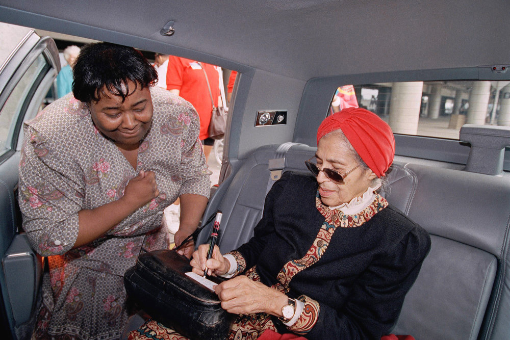 . Civil rights legend Rosa Parks, of Detroit, MI, signs an autograph for an emotional Joyce Hunter, left, of Queens, N.Y., after Mrs. Parks, arrived on July 12, 1992 at New York\'s LaGuardia Airport for the start of the Democratic National Convention in New York. (AP Photo/Alex Brandon)