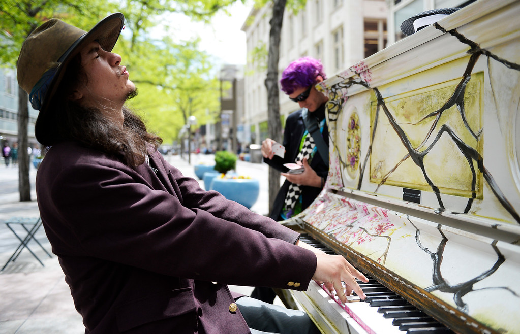 """. The pianos are back! The pianos are back! The \""""Your Keys to the City\"""", public art program pianos along the 16th Street Mall  have come out from winter hibernation in downtown Denver on Monday, May 09, 2016. Dante Love gets animated as he sits down and plays the piano as magician \""""The Hatter\"""" readies a card trick in the background at a piano at California Street.  (Photo by Cyrus McCrimmon/The Denver Post)"""