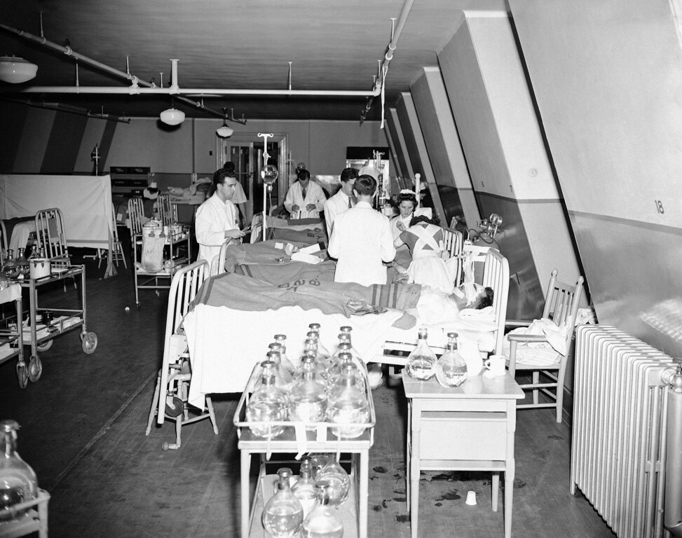 . Lieutenant Joseph Edelin, of Camp Edwards, Mass., receives a blood plasma transfusion at the Boston City Hospital, Nov. 30, 1942. Treating him are Dr. Karlin, Dr. Sexton and nurse Dorothy Manahan. Lt. Edelin was badly burned in the fire at the Cocoanut Grove Night Club in Boston on November 28. (AP Photo/Abe Fox)