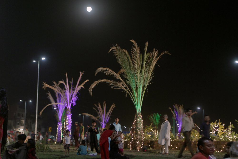 ". Pakistani families visit a park as a perigee moon, also known as a supermoon, rises in Lahore, Pakistan, Saturday, July 12, 2014. The phenomenon, which scientists call a ""perigee moon,\"" occurs when the moon is near the horizon and appears larger and brighter than other full moons. (AP Photo/K.M. Chaudary)"