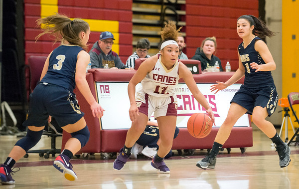 01/0719 Wesley Bunnell | StaffrrNew Britain girls basketball vs Newington at NBHS on Tuesday evening. Adriana Faienza (12) goes between Newingotn's Karissa Zocco (3) and Sabrina Soler (1).