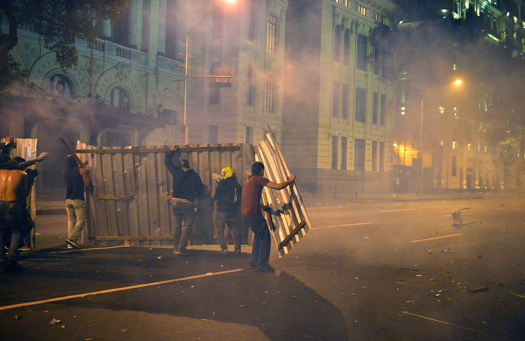 """. Demonstrators clash with the police after the \""""Teachers\' day\"""" protest in demand of better working conditions and against police violence, on October 15, 2013 in Rio de Janeiro, Brazil. AFP PHOTO / CHRISTOPHE SIMON/AFP/Getty Images"""