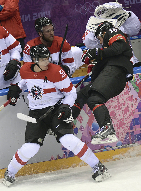 . Austria\'s Matthias Trattnig (L) sends Canada\'s Jonathan Toews overboard during the Men\'s Ice Hockey Group B match Canada vs Austria at the Bolshoy Arena during the Sochi Winter Olympics on February 14, 2014.  AFP PHOTO / ALEXANDER NEMENOV/AFP/Getty Images