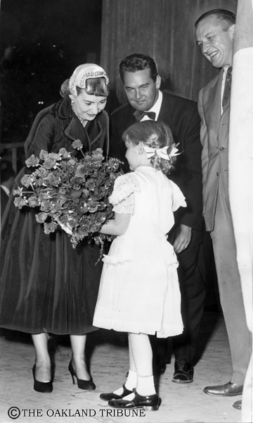. San Francisco, CA October 8, 1952  - Mamie Eisenhower receives flowers from a young girl at rally at San Francisco\'s Cow Palace. Next to Mamie from left is Russ Byrd, master of ceremonies, and U.S. Senator William F. Knowland. (Oakland Tribune Staff Archives)