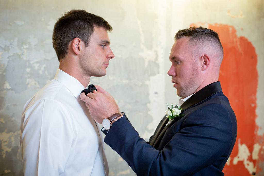 groomsman straightens a grooms bowtie