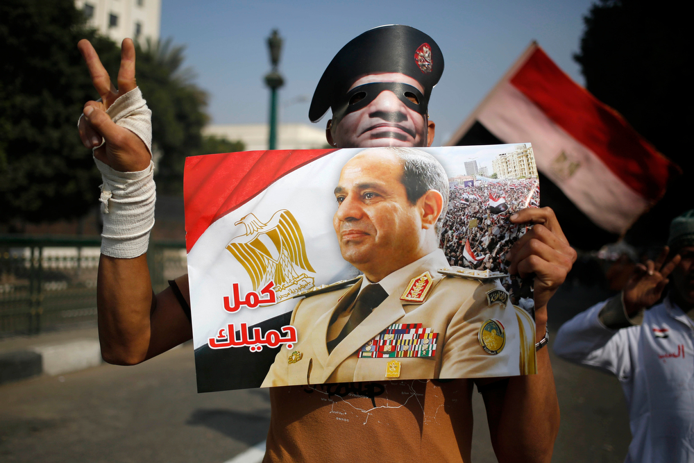 ". An Egyptian man holds a poster and a mask depicting Egyptian Defense Minister Gen. Abdel-Fattah el-Sissi with Arabic that reads, ""complete your good deed,\"" near Tahrir Square, the epicenter of the 2011 uprising, in Cairo, Egypt, Saturday, Jan. 25, 2014. Egyptian riot police have fired tear gas to disperse hundreds of supporters of ousted Islamist President Mohammed Morsi protesting as the country marks the third anniversary of the 2011 uprising, as supporters of the military gathered in rival rallies in other parts of the capital, many of them urging military chief el-Sissi, the man who removed Morsi, to run for president.(AP Photo/Hassan Ammar)"