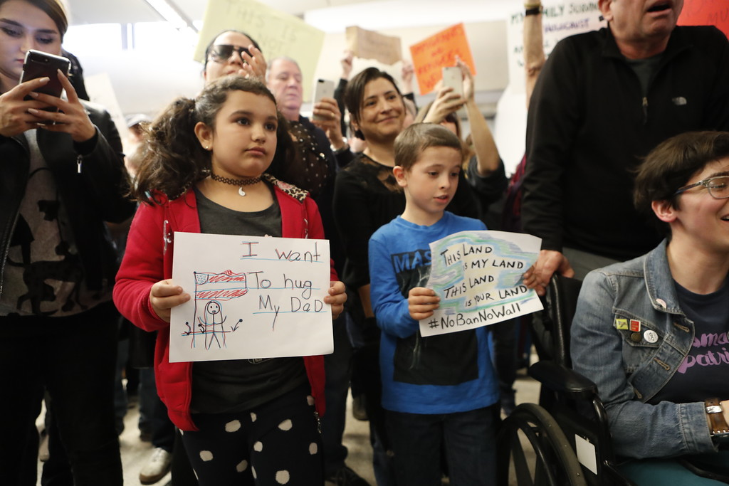 . Seven-year-old Teyom Karimi, left, holds a sign as protests against President Donald Trump\'s executive order banning travel from seven Muslim-majority countries continue at Los Angeles International Airport Sunday, Jan. 29, 2017. Karimi\'s father is currently detained in Iran. (AP Photo/Ryan Kang)