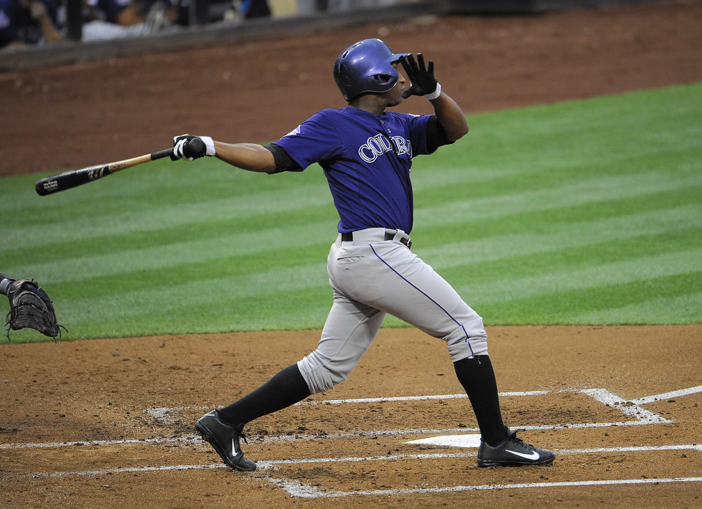 . Jonathan Herrera #18 of the Colorado Rockies hits a sacrifice fly during the second inning of a baseball game against the San Diego Padres at Petco Park on July 10, 2013 in San Diego, California.  (Photo by Denis Poroy/Getty Images)