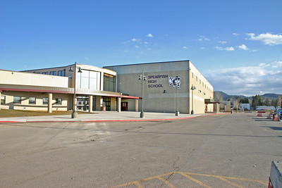 """There was much apprehension about just how difficult it would be to move to a new building after 53 years at the same location near Lookout Mountain.    Higbee says that the actual move -- during the Christmas holidays of 1979 -- employed about 400 people and a large pool of pickups.  The deed was done, he says, within four hours.  Even though it's called the """"new"""" high school, the newer facility west of North Main has been in use some 30 years.  Of course, there've been several additions to the building -- but it still has a nice vantage point, as witnessed by this view of Spearfish Mountain in the background.  Of course, it's hard to beat the terrific panorama that students and faculty enjoyed from the old high school building.  You can replace the school -- but not the memories!  To return to other recent Spearfish Area Historical Society topics and index, simply click  Spearfish History, or you can continue to scroll down through gallery photographs from previous presentations."""