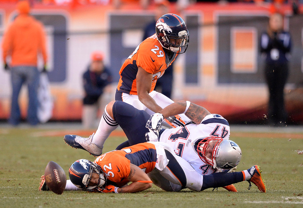 . New England Patriots tight end Michael Hoomanawanui (47) lands on Denver Broncos cornerback Tony Carter (32) after Carter nearly intercepted quarterback Tom Brady (12). The Denver Broncos vs. The New England Patriots in an AFC Championship game  at Sports Authority Field at Mile High in Denver on January 19, 2014. (Photo by John Leyba/The Denver Post)