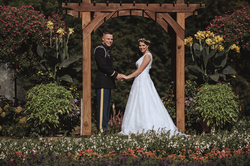The bride and groom posing under the garden arbor with flowers all around them.
