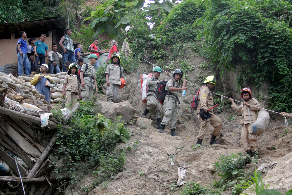 . Rescuers descend into a gold mine where miners are trapped inside after a landslide in San Juan Arriba, Choluteca in southern Honduras, early Thursday, July 3, 2014. The entrance to the artisanal mine has a vertical entrance, is located on a steep slope, and operated by local residents. (AP Photo/Fernando Antonio)