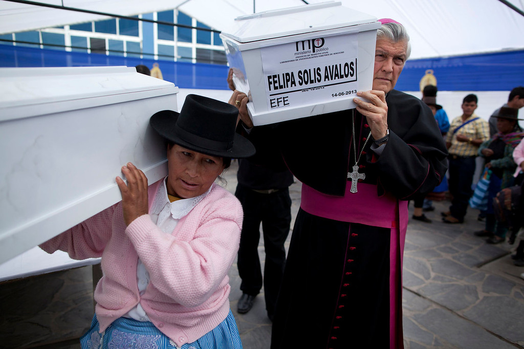 . Ayacucho Archbishop Salvador Pineiro helps to carry a coffin that contains the remains of a person killed in the 1988 Chaca massacre, to a waiting vehicle in Ayacucho, Peru. The relatives of villagers slain by Shining Path militants nearly three decades ago, formally buried the victims\' remains the following day in a mass burial at the local cemetery in Chaca. The remains were exhumed last year from a common grave in the remote Ayacucho state hamlet.   (AP Photo/Rodrigo Abd)