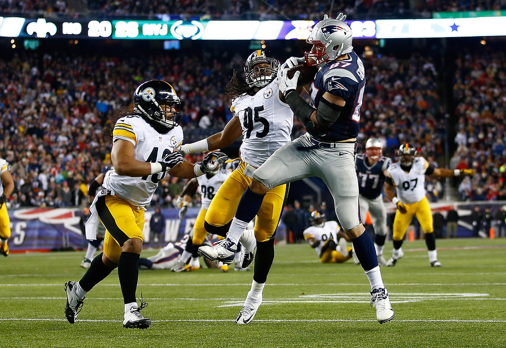 . Rob Gronkowski #87 of the New England Patriots catches a pass in front of Jarvis Jones #95 and Troy Polamalu #43 of the Pittsburgh Steelers in the second quarter before running in for a touchdown at Gillette Stadium on November 3, 2013 in Foxboro, Massachusetts.  (Photo by Jared Wickerham/Getty Images)