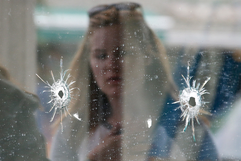 ". A woman looks at the bullet holes on the window of IV Deli Mark where Friday night\'s mass shooting took place by a drive-by shooter on Saturday, May 24, 2014, in Isla Vista, Calif. The shooter went on a rampage near a Santa Barbara university campus that left seven people dead, including the attacker, and seven others wounded, authorities said Saturday. Attorney Alan Shifman says the family of a man suspected in the shooting rampage called police several weeks ago after being alarmed by YouTube videos ""regarding suicide and the killing of people.\"" Shifman is the attorney for Peter Rodger, who was an assistant director on \""The Hunger Games\"" film series. Authorities have not confirmed the identity of the shooter.  (AP Photo/Jae C. Hong)"