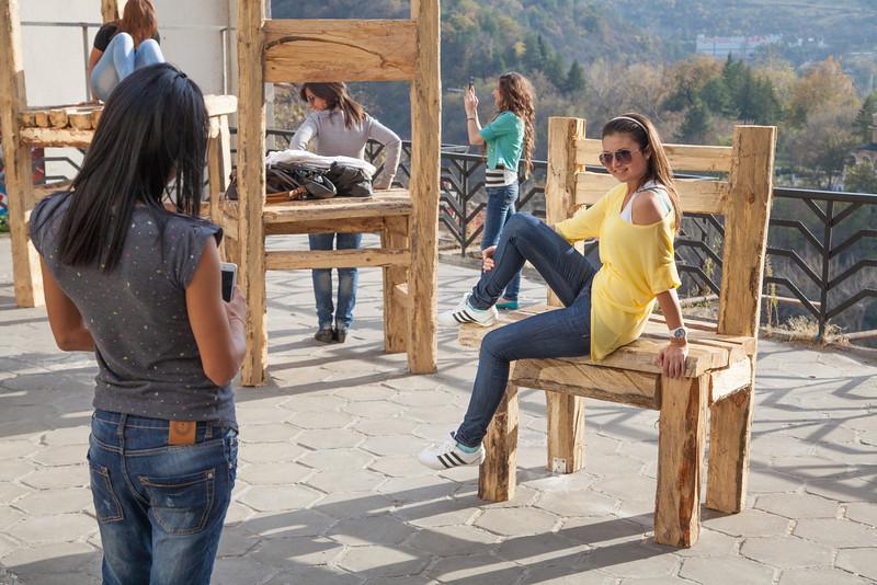 Yooung Bulgarian tourists pose on street sculptures in Veliko Tarnovo, Bulgaria.
