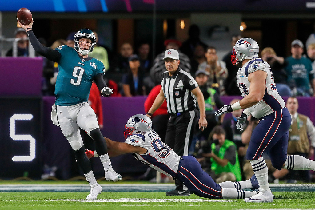 . Philadelphia Eagles\' Nick Foles (9) is pressured by New England Patriots\' Trey Flowers during the first half of the NFL Super Bowl 52 football game Sunday, Feb. 4, 2018, in Minneapolis. (AP Photo/Jeff Roberson)
