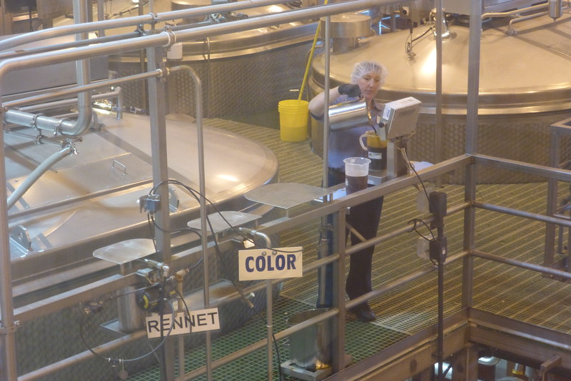 A worker adding color to the cheese batches.