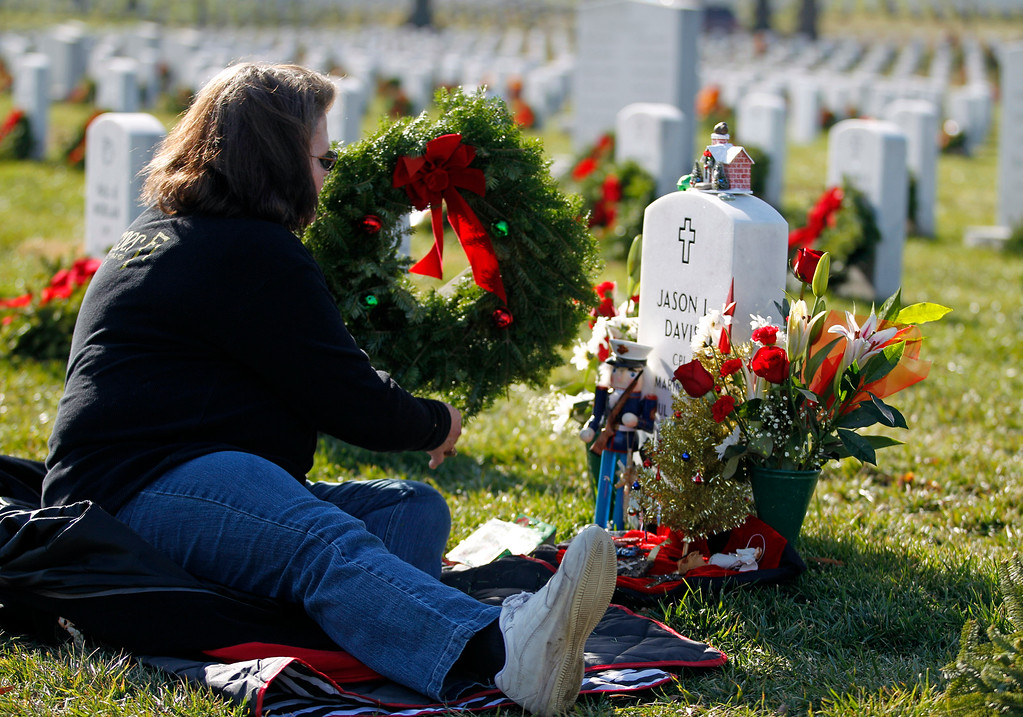 . The headstone of Marine Cpl. Jason Lee Davis is decorated by his mother Diane Travis during as she lays a holiday wreath at graves at Arlington National Cemetery in Arlington, Va., Saturday Dec. 15, 2012, during Wreaths Across America Day. Wreaths Across America was started in 1992 at Arlington National Cemetery by Maine businessman Morrill Worcester and has expanded to hundreds of veterans\' cemeteries and other locations in all 50 states and beyond. (AP Photo/Jose Luis Magana)