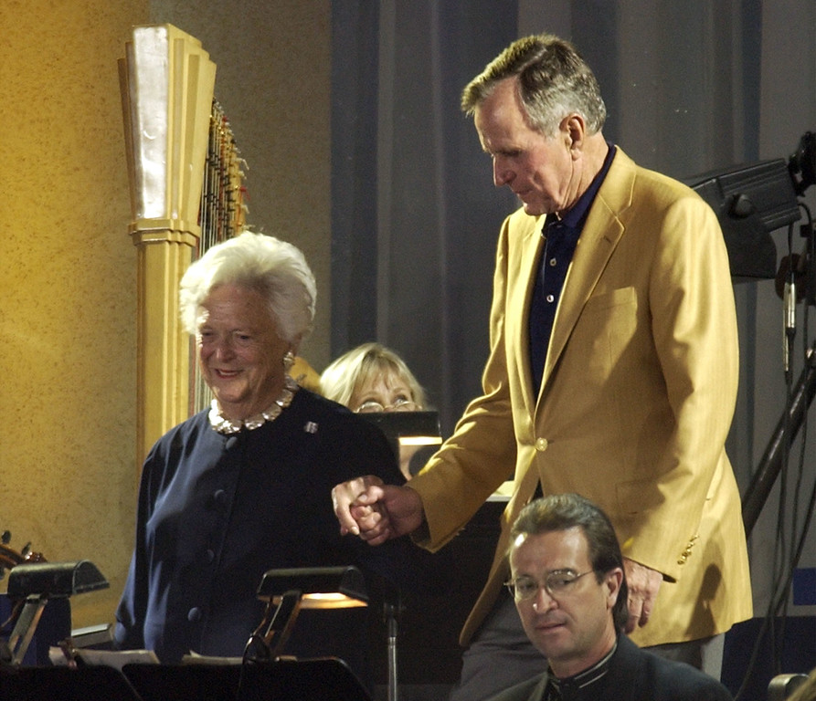 . Former President George H.W. Bush walks with his wife Barbara Bush at the start of his  80th birthday celebration at Minute Maid Park in Houston, Texas Saturday, June 12, 2004. (AP Photo/Gerald Herbert)