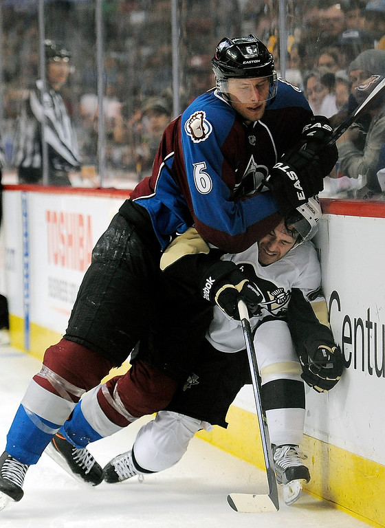. Colorado Avalanche defenseman Erik Johnson, top, checks Pittsburgh Penguins center Brian Gibbons against the boards during the second period of an NHL hockey game Sunday, April 6, 2014, in Denver.  (AP Photo/Chris Schneider)
