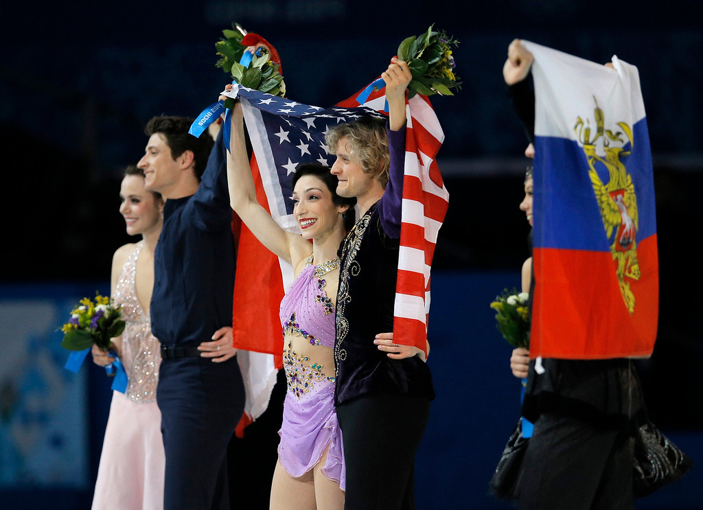 . Meryl Davis and Charlie White of the United States, centre, Tessa Virtue and Scott Moir of Canada, left, and Elena Ilinykh and Nikita Katsalapov of Russia pose for photographers during the flower ceremony for the ice dance free dance figure skating finals at the Iceberg Skating Palace during the 2014 Winter Olympics, Monday, Feb. 17, 2014, in Sochi, Russia. Davis and White placed first, Virtue and Moir second, with Ilinykh and Katsalapov third. (AP Photo/Vadim Ghirda)