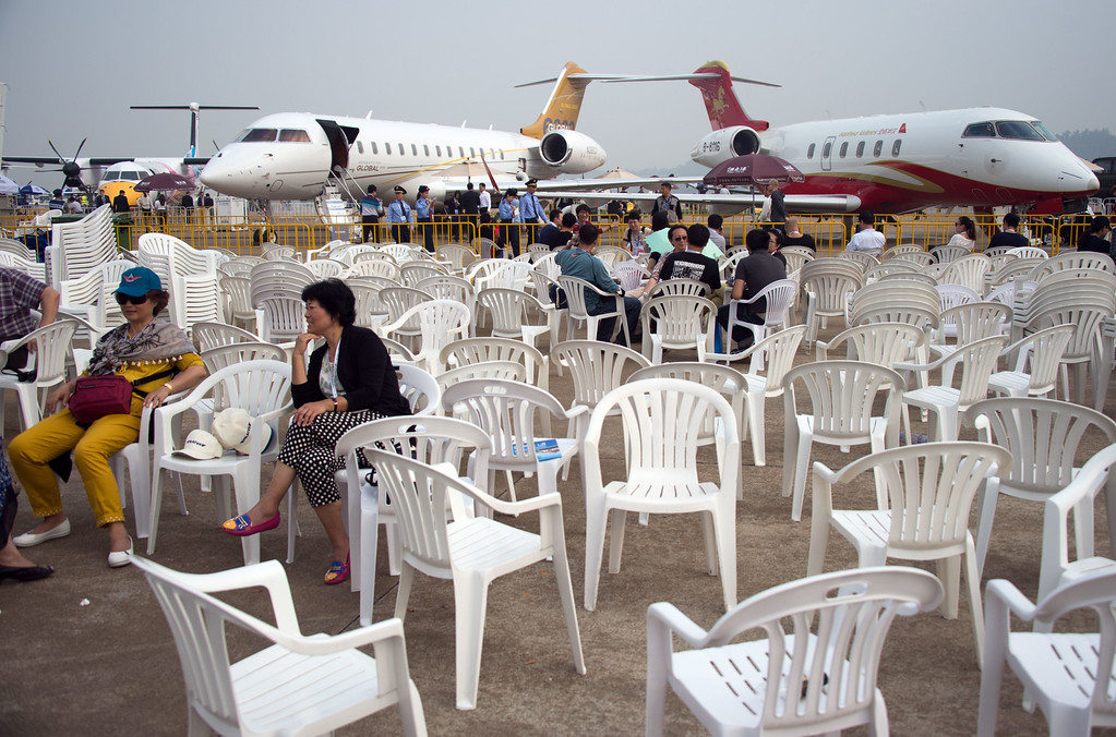 . Spectators take a rest in front of a Bombardier Challenger 300 (R) and Bombardier Challenger Global 6000 business aircrafts on display at the Airshow China 2014 in Zhuhai, south China\'s Guangdong province on November 11, 2014. Global aviation firms flocked to China on November 11 to show off their wares as economic development and an expanding middle class promise a bonanza in one of the world\'s fastest-growing aircraft markets.  AFP PHOTO / JOHANNES EISELE/AFP/Getty Images