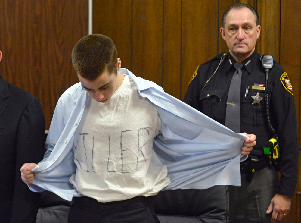 Description of . T.J. Lane unbuttons his shirt during sentencing on Tuesday, March 19, 2013, in Chardon, Ohio.  Lane was given three lifetime prison sentences without the possibility of parole Tuesday for opening fire last year in a high school cafeteria in a rampage that left three students dead and three others wounded.  Lane, 18, had pleaded guilty last month to shooting at students in February 2012 at Chardon High School, east of Cleveland. Investigators have said he admitted to the shooting but said he didn't know why he did it. Before the case went to adult court last year, a juvenile court judge ruled that Lane was mentally competent to stand trial despite evidence he suffers from hallucinations, psychosis and fantasies. (AP Photo/The News-Herald, Duncan Scott, Pool)