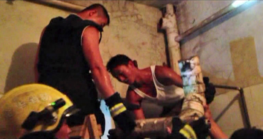 . In this still image taken from video from Saturday May 25, 2013, a firefighter  removes a section of a sewage pipe where a newborn baby appears trapped, in Pujiang in east China\'s Zhejiang province. (AP Photo)