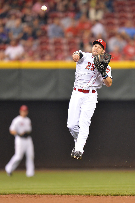 . CINCINNATI, OH - MAY 10: Skip Schumaker #25 of the Cincinnati Reds makes a throw to first base after chasing down a ground ball against the Colorado Rockies in the eighth inning at Great American Ball Park on May 10, 2014 in Cincinnati, Ohio. The throw was not in time and the runner was safe at first base as Colorado defeated Cincinnati 11-2. (Photo by Jamie Sabau/Getty Images)
