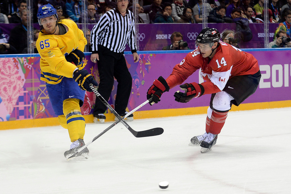 . Erik Karlsson (65) of Sweden takes a shot as Chris Kunitz (14) of Canada defends during the second period of the men\'s ice hockey gold medal game. Sochi 2014 Winter Olympics on Sunday, February 23, 2014 at Bolshoy Ice Arena. (Photo by AAron Ontiveroz/ The Denver Post)