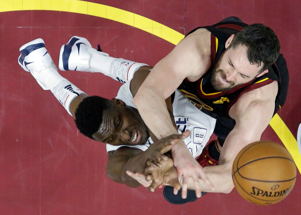 . Washington Wizards\' Ian Mahinmi, left, from France, blocks a shot by Cleveland Cavaliers\' Kevin Love in the first half of an NBA basketball game, Thursday, April 5, 2018, in Cleveland. (AP Photo/Tony Dejak)