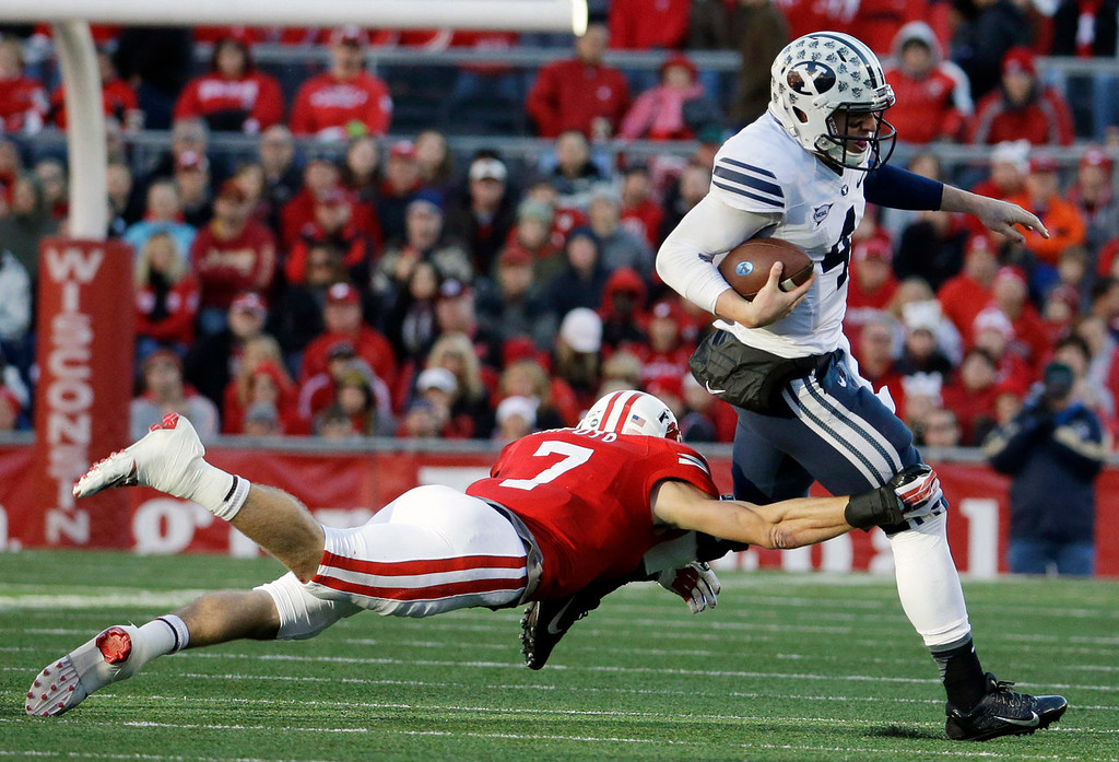 . Brigham Young\'s Taysom Hill, right, tries to break away from Wisconsin\'s Michael Caputo during the first half of an NCAA college football game on Saturday, Nov. 9, 2013, in Madison, Wis. (AP Photo/Morry Gash)