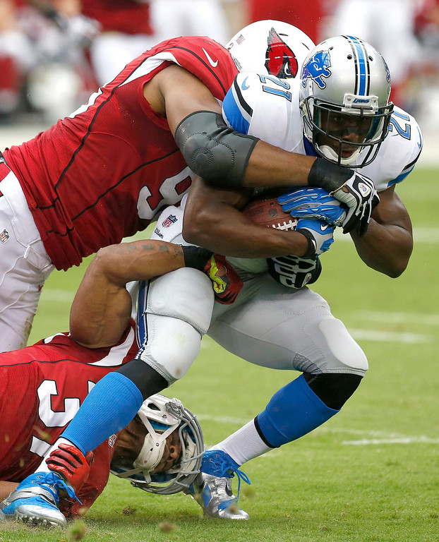 . Detroit Lions running back Reggie Bush (21) is tackled by Arizona Cardinals defensive end Calais Campbell, left, and Yeremiah Bell, bottom, during the first half of a NFL football game, Sunday, Sept. 15, 2013, in Glendale, Ariz. (AP Photo/Ross D. Franklin)