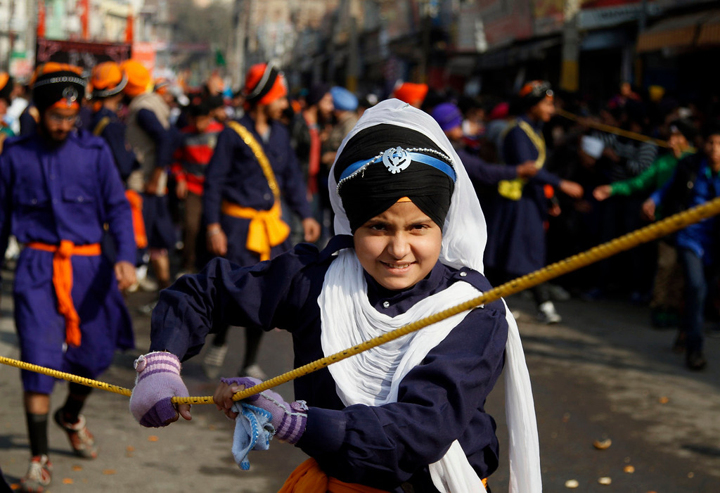 . A young India Sikh girl volunteer guards a religious procession ahead of the birth anniversary of Guru Gobind Singh in Jammu, India, Saturday, Jan. 4, 2014. The birth anniversary of Guru Gobind Singh, the tenth Sikh guru, will be marked on Jan. 7 this year. (AP Photo/Channi Anand)