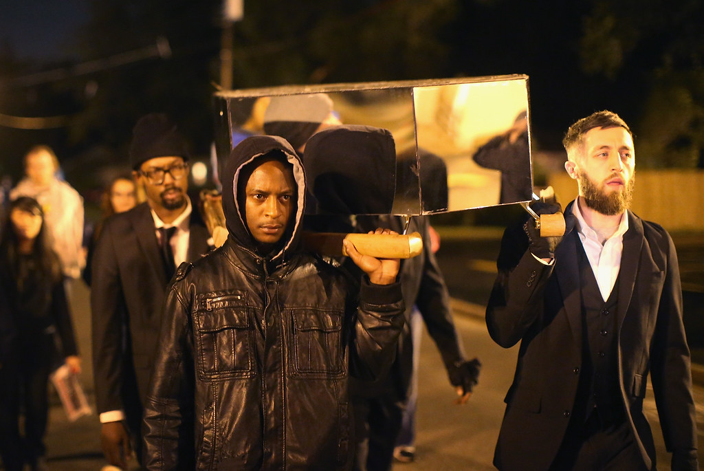 . FERGUSON, MO - OCTOBER 10:  Demonstrators carry a mock coffin during a protest outside the Ferguson police department on October 10, 2014 in Ferguson, Missouri. Ferguson has been plagued with protests which have sometimes turned violent since the death of 18-year-old Michael Brown who was shot and killed by Darren Wilson, a Ferguson police officer, on August 9.  (Photo by Scott Olson/Getty Images)