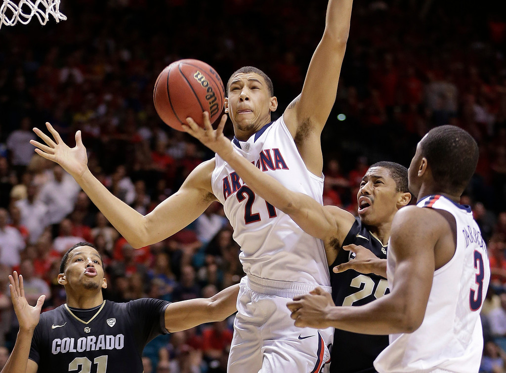 . Colorado\'s Spencer Dinwiddie (25) puts up a shot between Arizona\'s Brandon Ashley (21) and Kevin Parrom in the second half during a Pac-12 tournament NCAA college basketball game, Thursday, March 14, 2013, in Las Vegas. Arizona won 79-69. (AP Photo/Julie Jacobson)