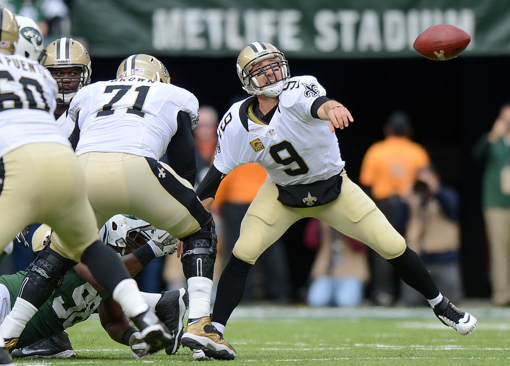 . Quarterback Drew Brees #9 of the New Orleans Saints throws left handed as he is being pulled down in the 1st  quarter against the New York Jets at MetLife Stadium on November 3, 2013 in East Rutherford, New Jersey. (Photo by Ron Antonelli/Getty Images)