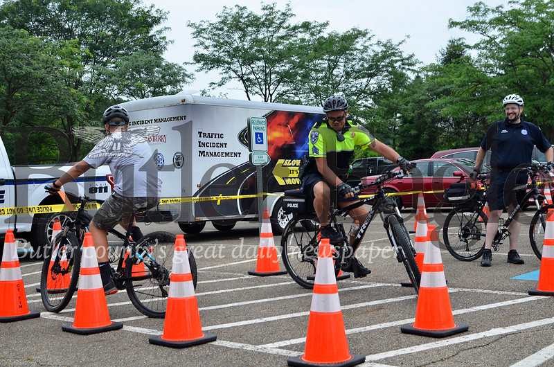 Sgt. Bill Ahlgren of the Cranberry Township Police Department rides through one of the bicycle course's obstacles with Brody Schmitt, 13, Cranberry Township.