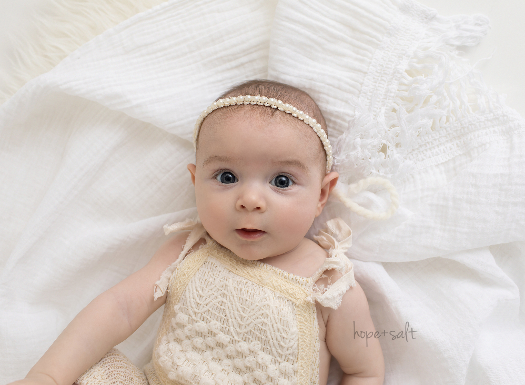 burlington baby photographer - 4 month old girl Quinn in studio session with all white blankets wrapped like a newborn